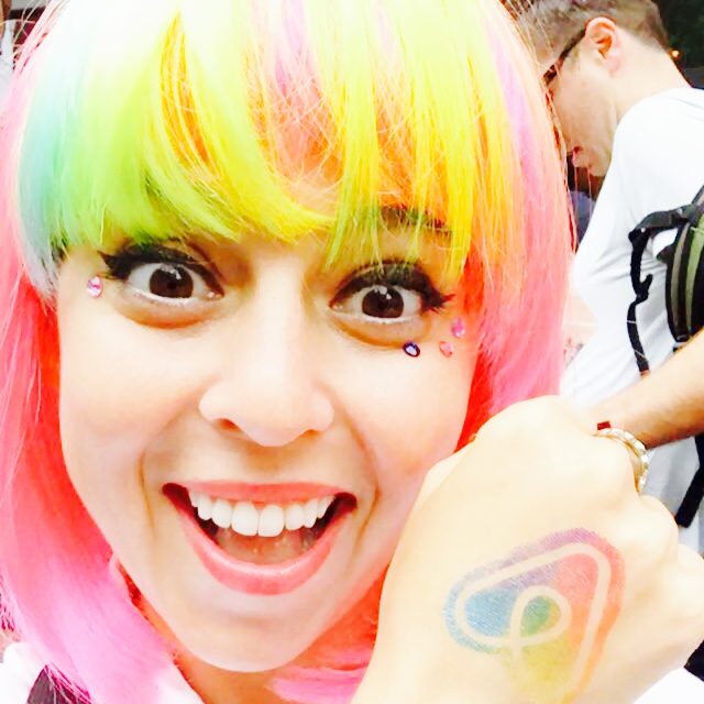 nina mufleh in a rainbow colored wig showing off the airbnb host with pride logo.